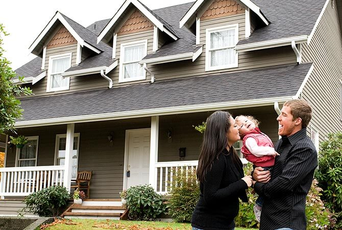 Young couple holding their small child in front of their new home
