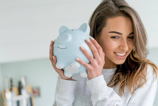 Young adult woman holding a piggy bank to her ear