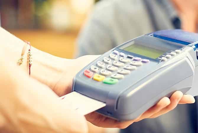 person holding merchant credit card reader and inserting a chip credit card