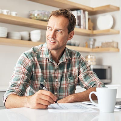 Middle age man going over retirement paperwork in kitchen