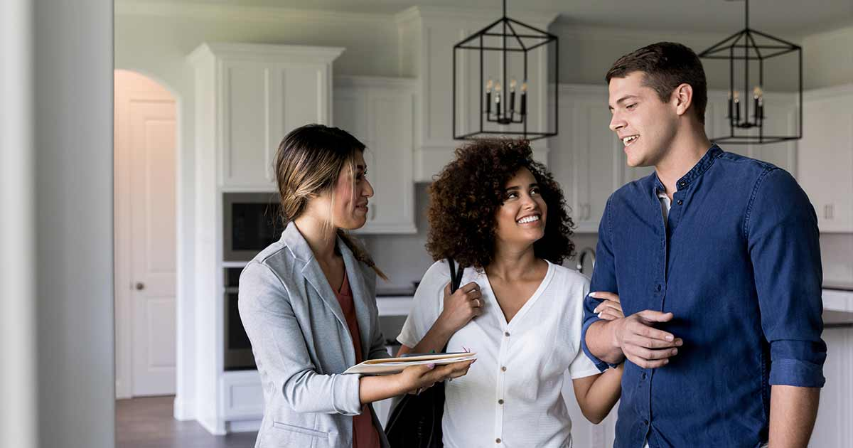 Happy couple looking at first home with realtor